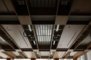 Ceiling with veneered timber panels and exposed services